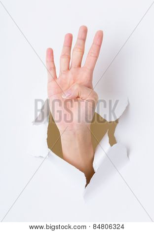 Four finger breaking through paper wall
