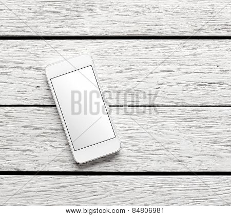 White smart phone on white wooden desk. Clipping path included.