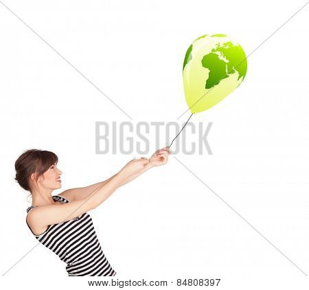 Happy young lady holding a green globe balloon