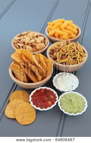 Savoury snack and dip party food selection in wooden bowls and porcelain dishes.