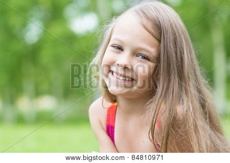Cheerful little girl on a background of greenery in the park. Girl seven years.