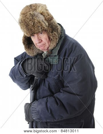 Close-up of a bundled senior man, grumpy as he leans on the handle of he snow shovel.  On a white background.