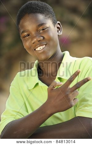 Close-up image of a happy young Haitian teen boy gesturing