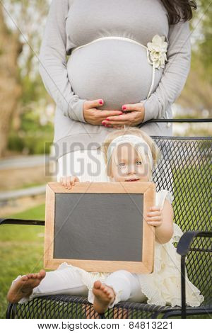 Pregnant Mom Behind Cute Baby Girl Sitting in Chair Holding Blank Blackboard.