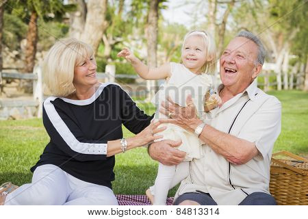 Affectionate Granddaughter and Grandparents Playing Outside At The Park.