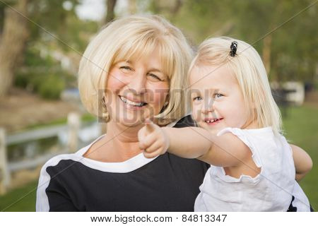Affectionate Grandmother and Granddaughter Playing Outside At The Park.