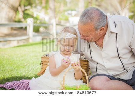 Loving Grandfather and Granddaughter Enjoying Easter Eggs on a Picnic Blanket At Park.