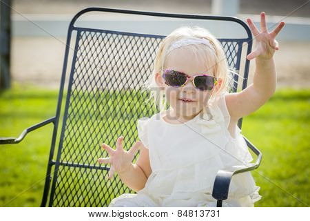 Cute Playful Baby Girl Wearing Sunglasses Outside at the Park.