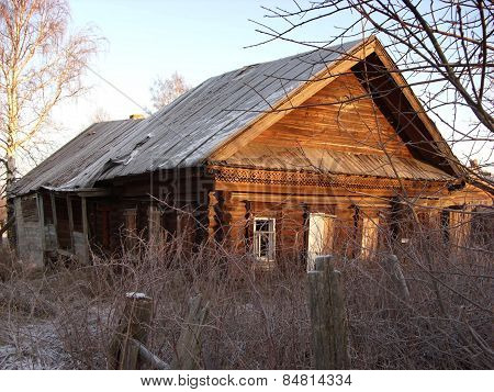 Ruined Rustic Wooden House In The Rays Of Winter Sun