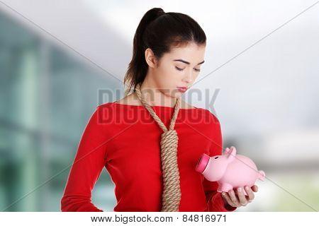 Worried woman holding a piggybank