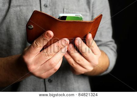 Man holding hand made leather wallet with money and cards on black  background