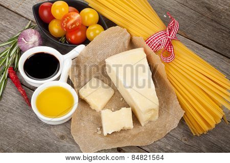 Parmesan cheese, pasta, tomatoes, vinegar, olive oil, herbs and spices on wooden table background