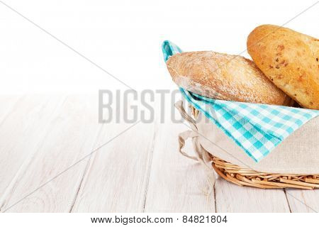 Fresh french bread in basket over white wooden table