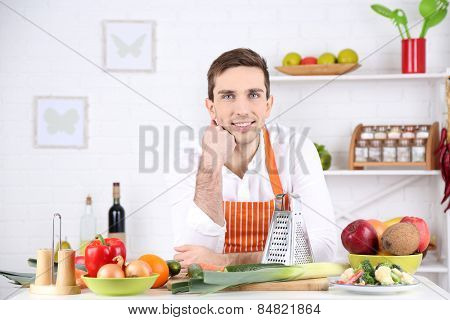 Man at table with different products and utensil in kitchen on white wall background