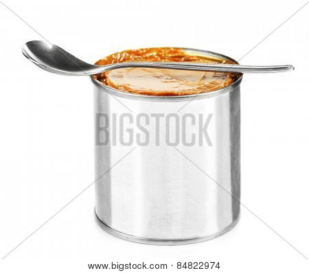 Can of boiled condensed milk with spoon isolated on white