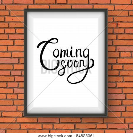Coming Soon Texts in a Frame Hanging on Brick Wall