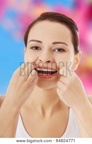 Beautiful woman flossing her teeth