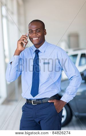 happy salesman talking on mobile phone in vehicle showroom