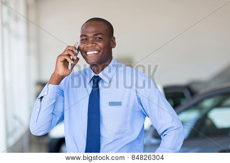african american car salesman talking on cell phone in showroom