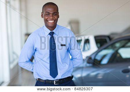 good looking afro american salesman working at vehicle showroom