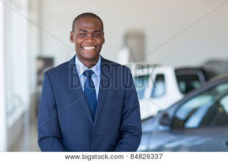 portrait young african businessman in car showroom