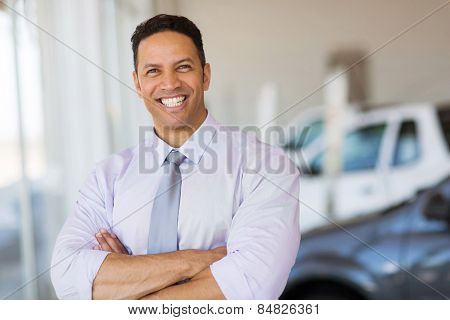 cheerful vehicle dealership principal with arms crossed in showroom