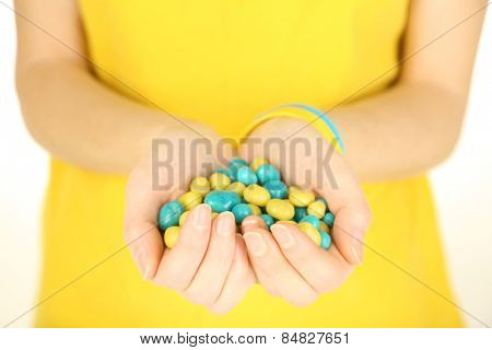 Woman holding blue-yellow candies - colors of flag of Ukraine, isolated on white