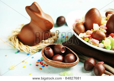 Chocolate Easter eggs and rabbit on plate, on color wooden background