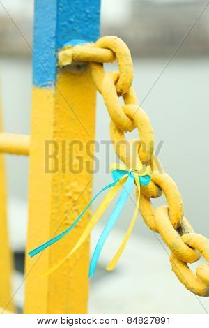 Blue-yellow bow on metal chain - colors of flag of Ukraine