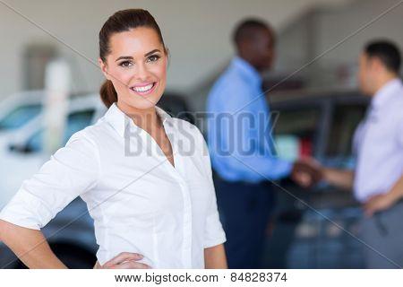 pretty female car dealer inside showroom