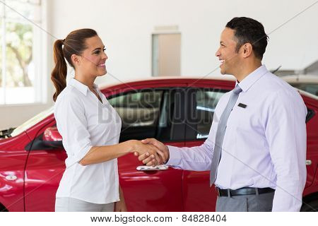 cheerful middle aged car dealer handshake with customer in showroom