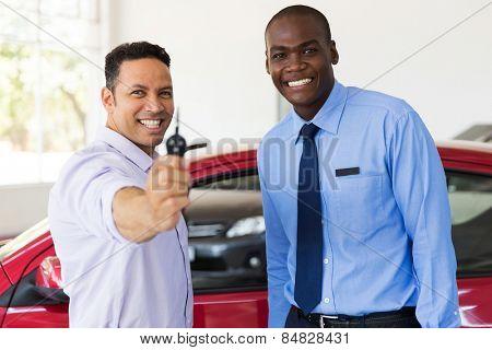 mid age man showing new car key at dealership