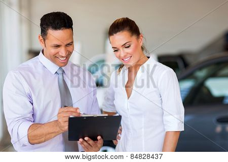 handsome vehicle dealership principal and saleswoman looking at clipboard
