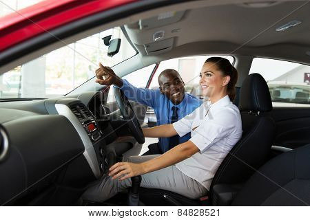happy salesman explaining car features to young female customer