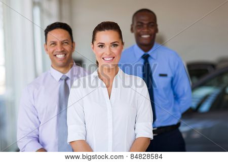 beautiful young female car dealer with colleagues on background