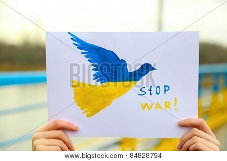 Hand holding paper dove with painted Ukraine flag