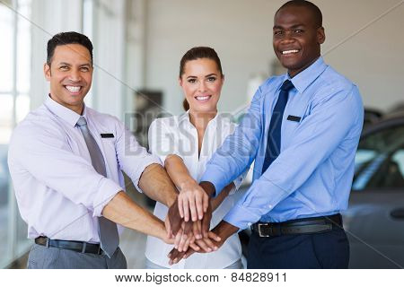 successful car dealership staff putting their hands together