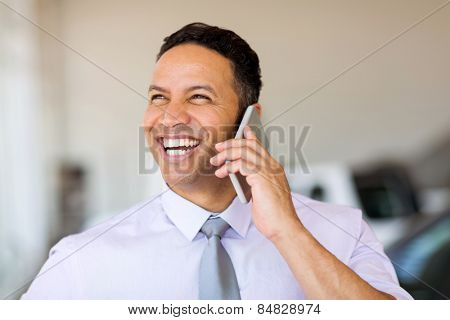 cheerful businessman talking on cell phone
