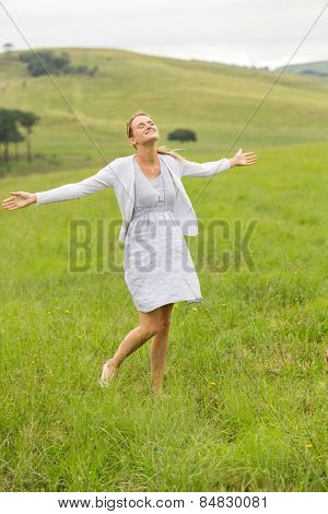 beautiful carefree young woman arms open in grassland