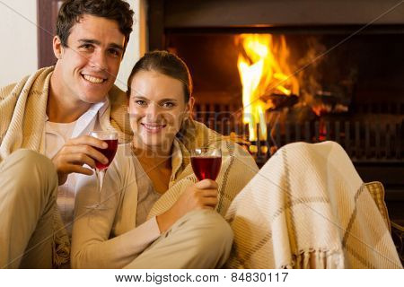 portrait of young couple drinking red wine in front of fireplace