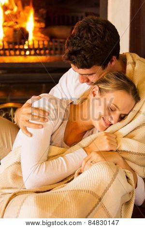 affectionate couple wrapped in blanket at home by fireplace