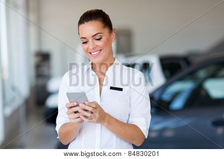 beautiful young car sales consultant using smart phone at showroom