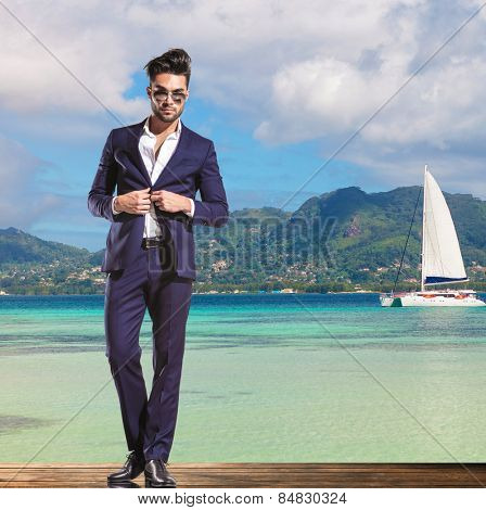handsome young business man wearing sunglasses is unbuttoning his suit while standing on a deck on the shore of the sea, little boat sailing in the background