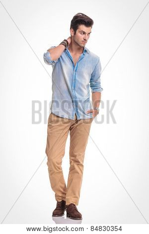 Attractive fashion man walking on studio background with one hand in his pocket while looking away from the camera.