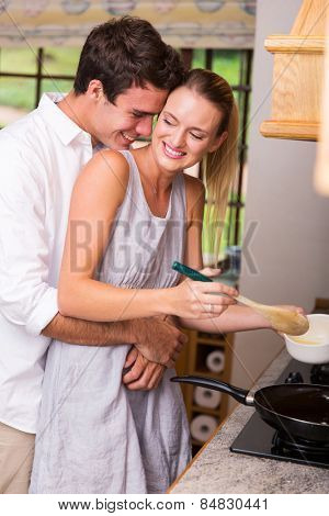 lovely young couple cooking together in kitchen