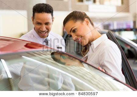friendly middle aged vehicle dealer showing young woman new car