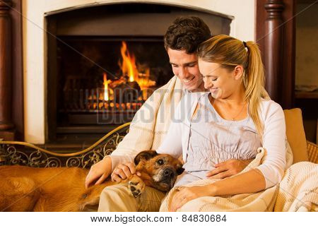 beautiful young couple sitting by fireplace with their pet dog at home