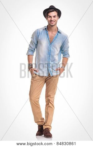 Happy young fashion man smiling at the camera while holding both hands in his pockets, full body picture.