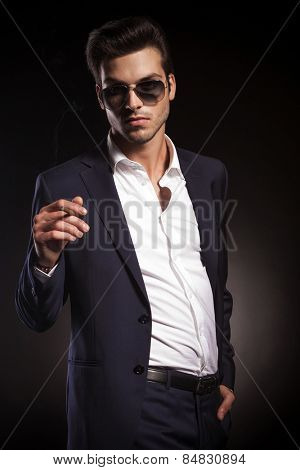 Portrait of a young elegant business man looking at the camera while smoking a cigarette.
