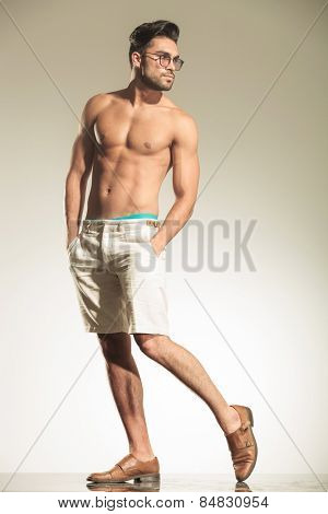 Full body picture of a shirtless man posing on studio background holding both hands in his pocket while looking back.